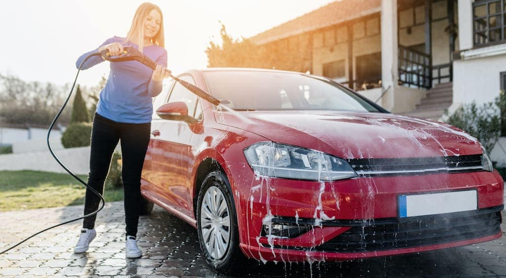 A woman is washing her red car in the driveway.