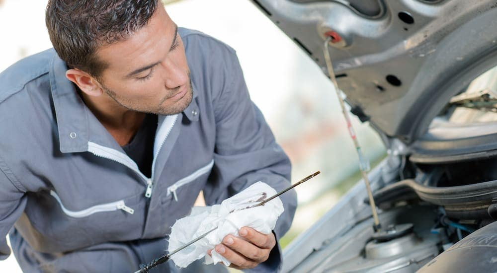 A mechanic is checking the oil level during a Nissan maintenance.
