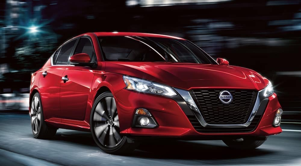 A red 2021 Nissan Altima is driving through a city at night.