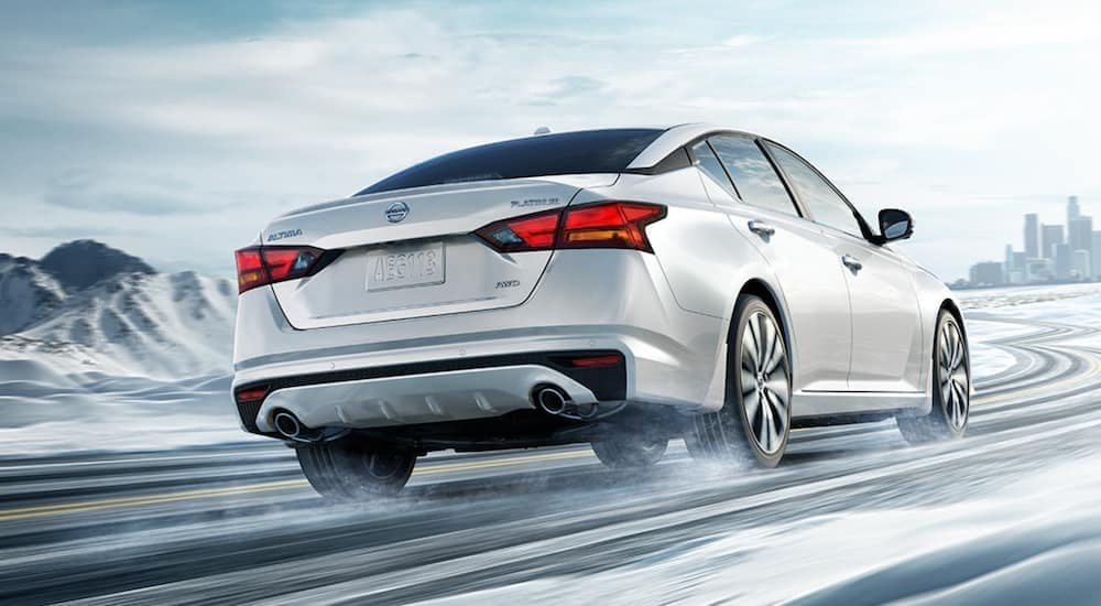 A white 2021 Nissan Altima is shown from behind driving down a snowy road after leaving a Nissan Altima dealer.
