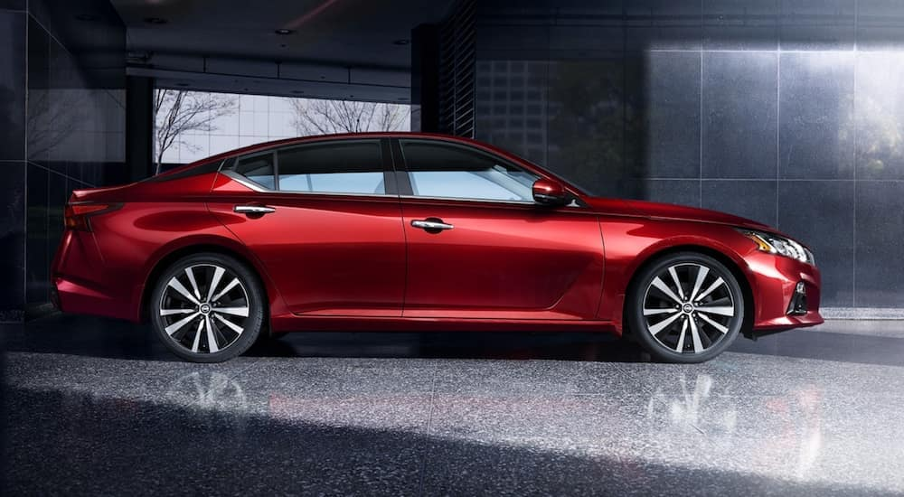 A red 2021 Nissan Altima is shown from the side parked in a show room.