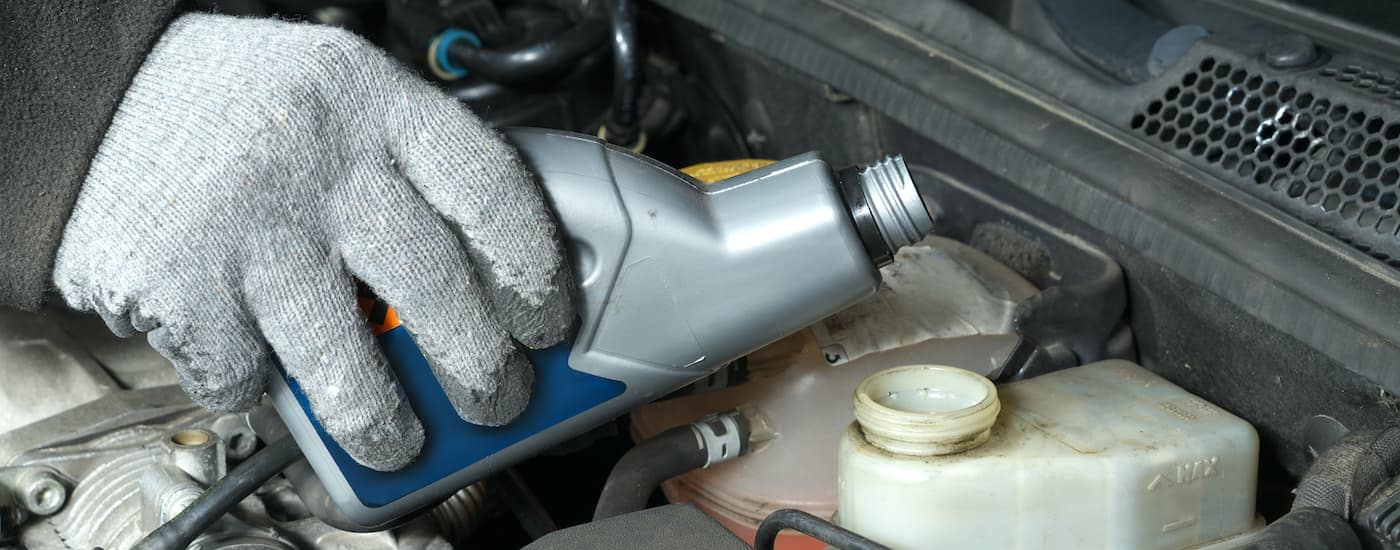 A close up shows a gloved hand filling a reservoir with brake fluid.