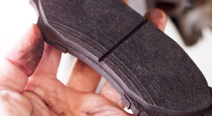 A close up shows wear on a brake pad.