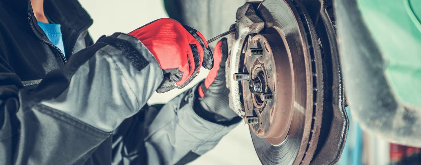 A close up shows a mechanic working on a caliper during a Nissan brake service.