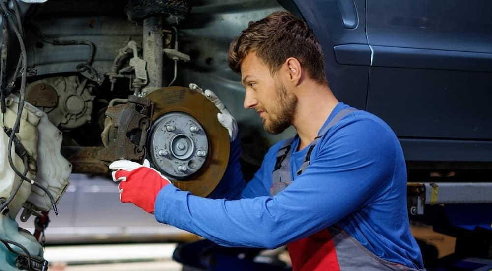 A mechanic is changing a brake pad during a Nissan brake service.