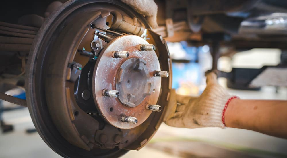 A close up shows a Nissan brake service being done by a gloved mechanic.