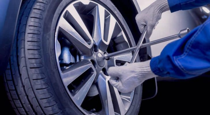 A gloved mechanic is taking a tire off of a car at a Chicagoland tire shop.