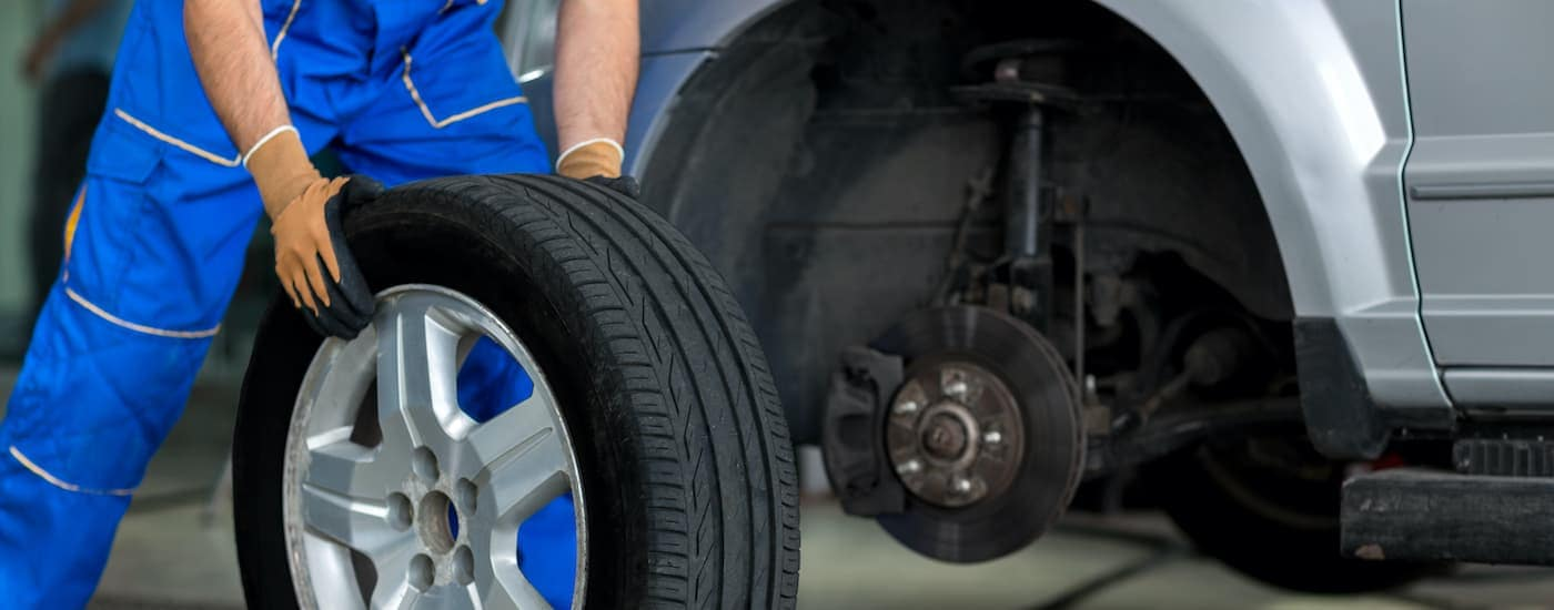 A gloved mechanic is placing a tire onto a car at a Chicagoland tire shop.