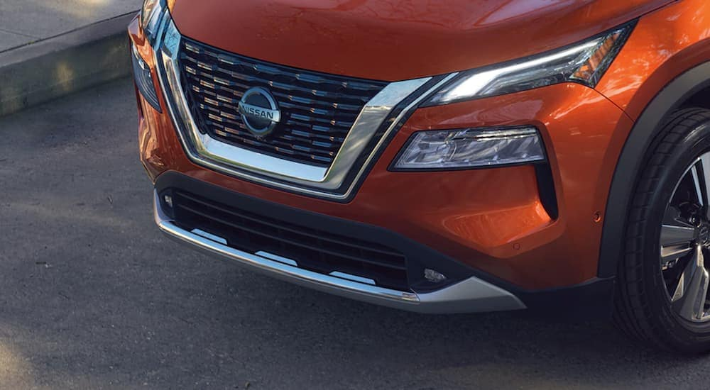 An orange 2021 Nissan Rogue shows a close up of the front grille.