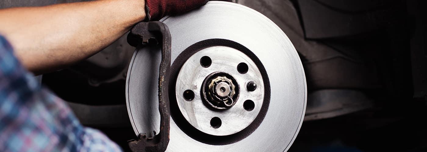 Car mechanic Repairing brakes on car. He is changing brake disc