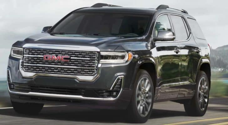 A grey 2021 GMC Acadia is driving past a body of water and a hill.