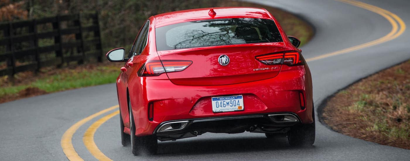 A red 2019 Buick Regal GS is shown from the rear driving down a winding road after leaving a Charlotte used car dealer.