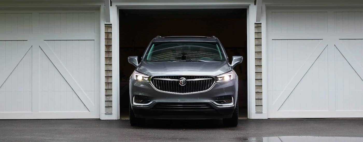 A silver 2020 Buick Enclave is shown driving out of a garage.