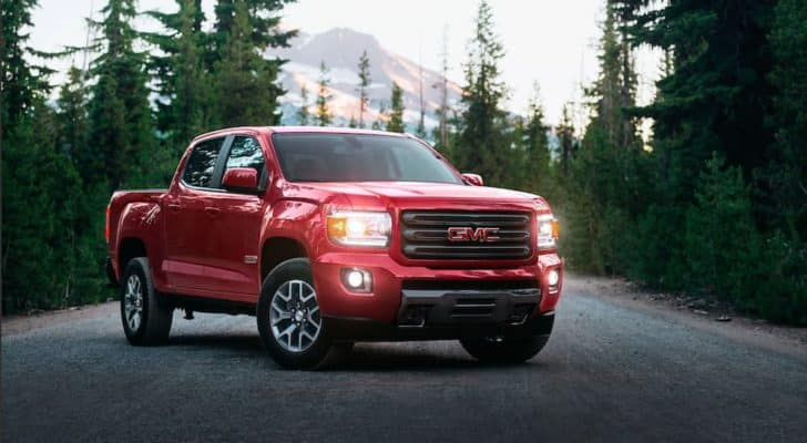 A red 2020 GMC Canyon All Terrain is shown parked on an empty road.