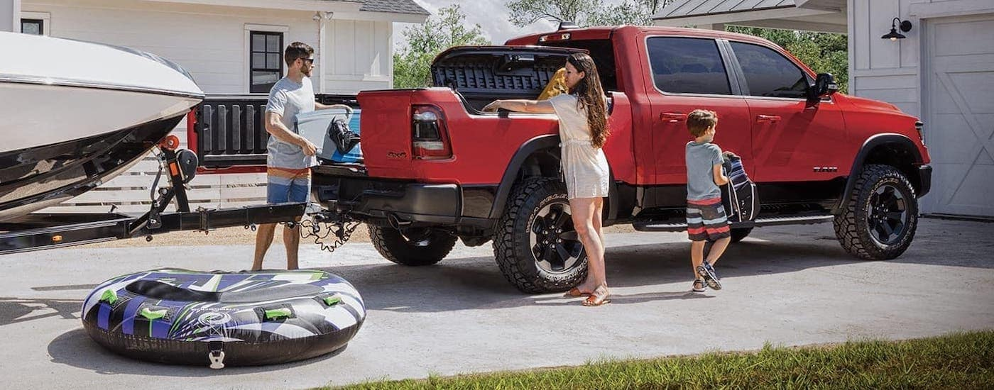 A family is loading up a red Ram 1500 for a boating trip.