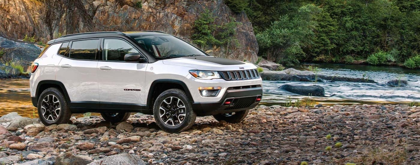 A white and black 2020 Jeep Compass is parked on a rocky river shore after leaving a Jeep dealer near me.