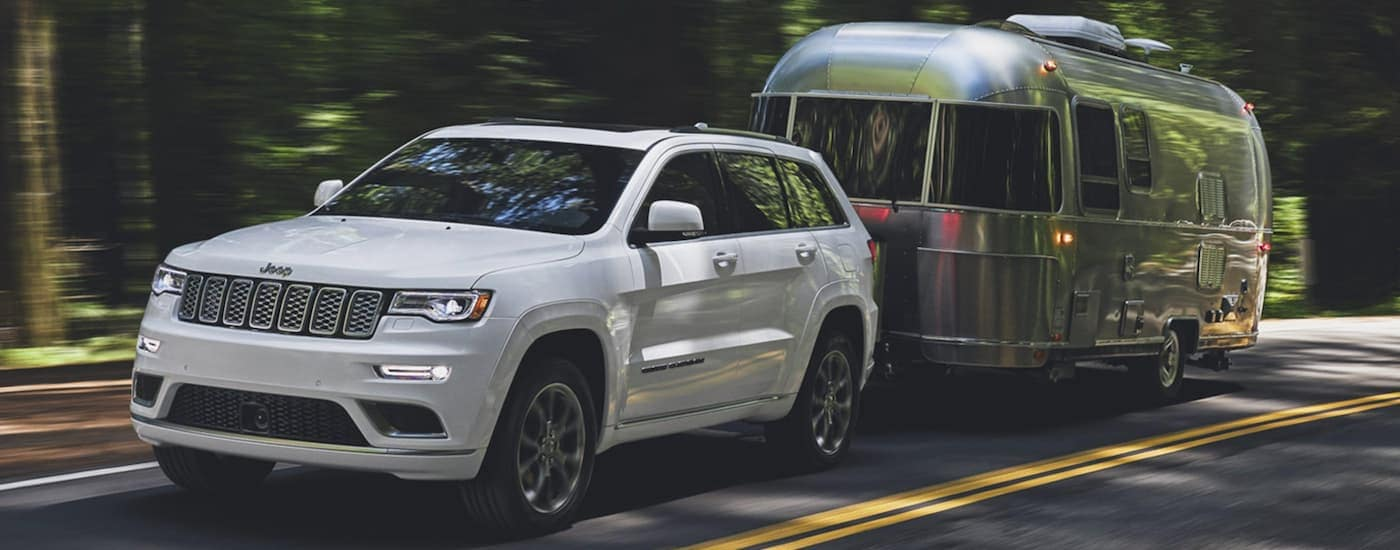 A white 2020 Jeep Grand Cherokee is towing an Airstream.