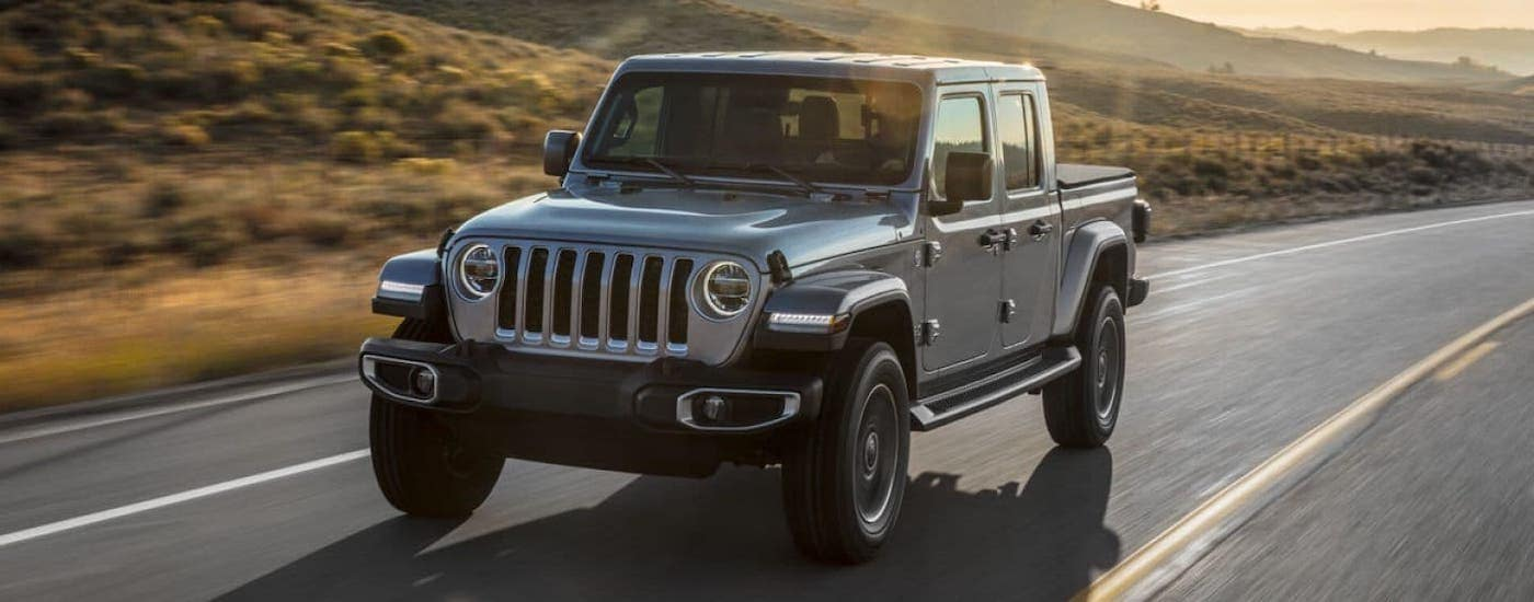 A silver 2020 Jeep Gladiator is driving on a highway at dusk.
