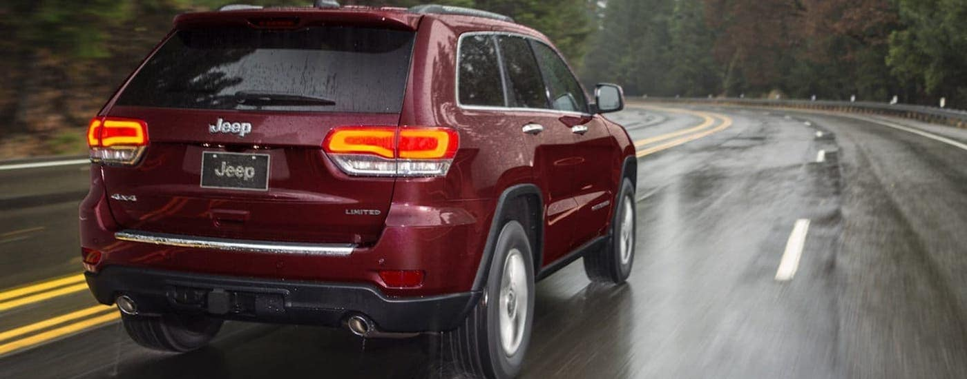 A red 2020 Jeep Grand Cherokee from a Jeep dealer near me is driving in the rain outside Florence, KY.