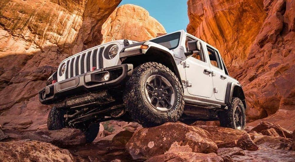 A white Jeep Wrangler Unlimited is parked on a rock formation.