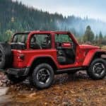 A red 2020 Jeep Wrangler is crossing a river in the mountains. See one at a Jeep dealer near me.