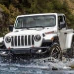 A white 2021 Jeep Wrangler, one of the new Jeeps for sale, is crossing a river while off-roading.