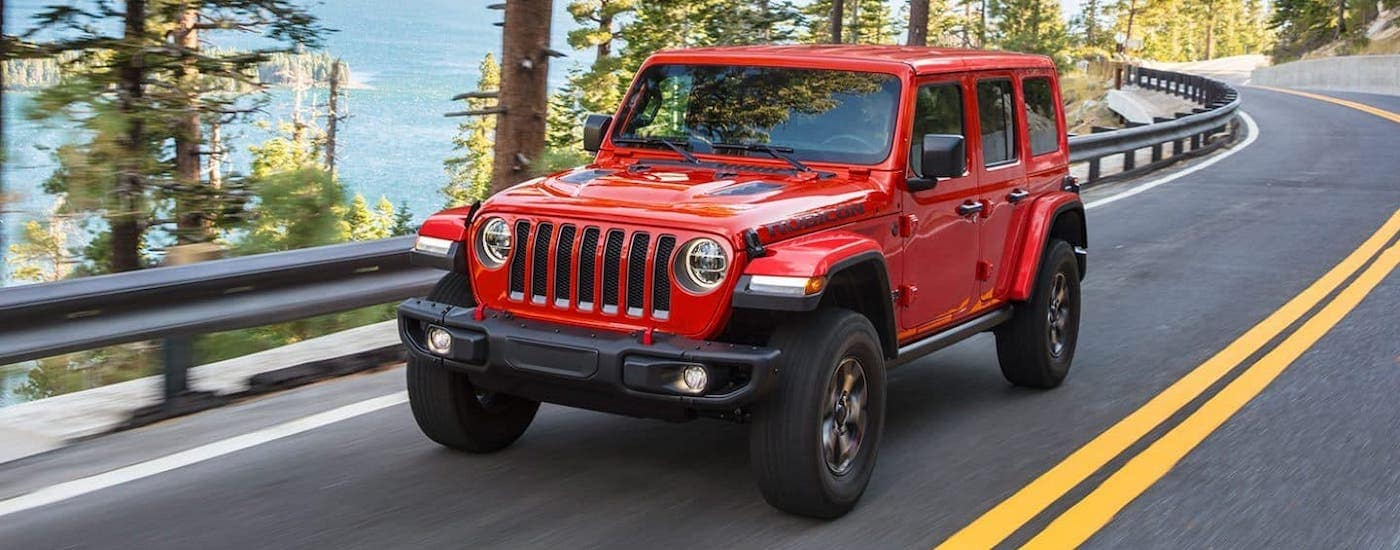 A red 2021 Jeep Wrangler Unlimited Rubicon is driving on a highway.