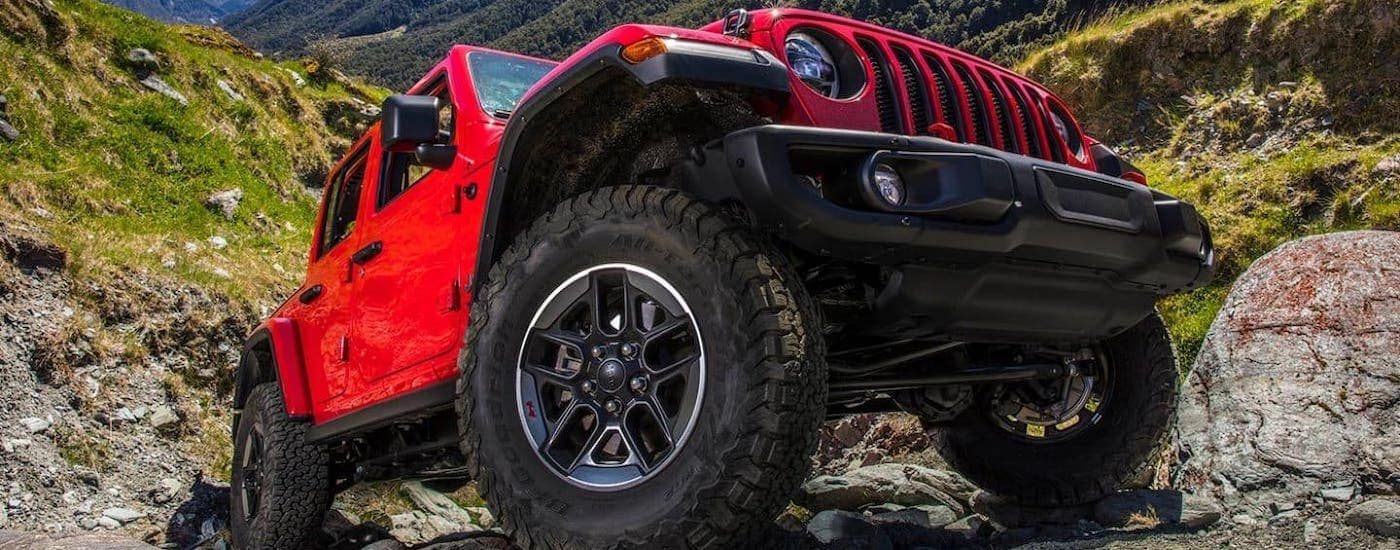 A closeup shows the tire on a red 2021 Jeep Wrangler Unlimited that is climbing over a rock.