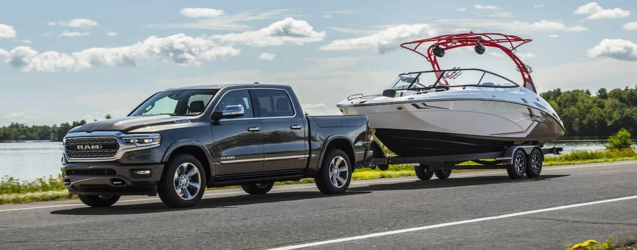 A grey 2021 Ram 1500 is towing a white boat.