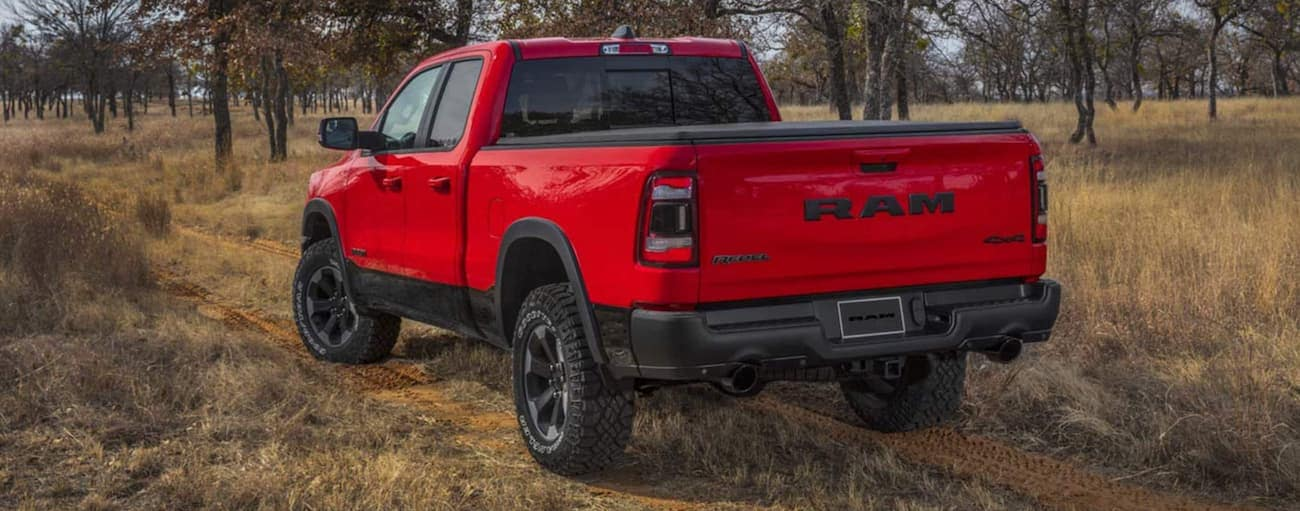 A red 2021 Ram 1500 Rebel is shown from the rear on a dirt road.