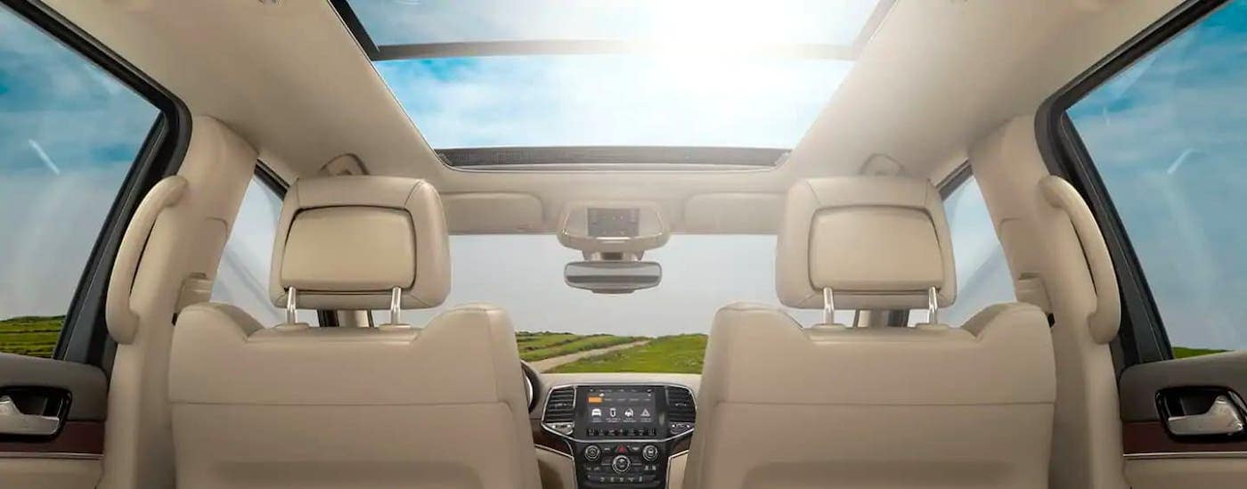 The moonroof and tan interior of a 2021 Jeep Grand Cherokee is shown from the rear seat.