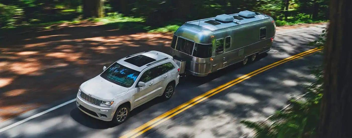 A white 2021 Jeep Grand Cherokee is shown from a high angle towing an Airstream camper on a road through the woods.