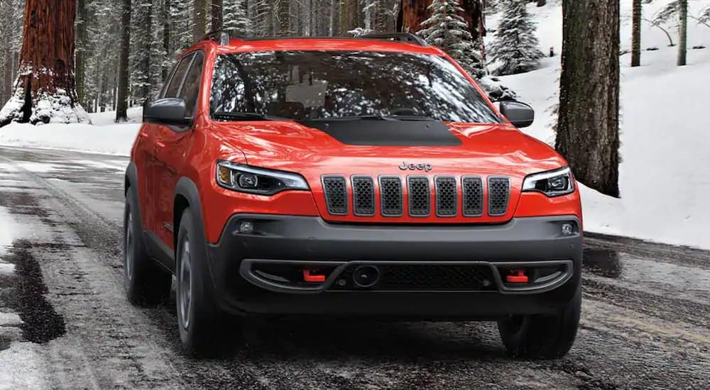 A red 2020 Jeep Cherokee, a popular used Jeep for sale in Cincinnati, is driving on a snow-lined road.