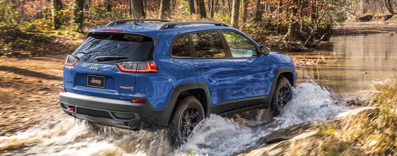 A blue 2021 Jeep Cherokee is off-roading through water in the woods.
