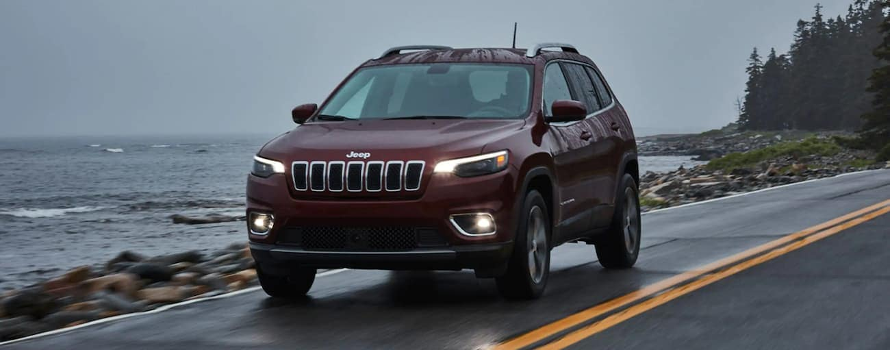 A burgundy 2021 Jeep Cherokee is driving past the ocean in the rain.