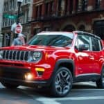A popular model for many Jeep dealers in Ky, a red 2021 Jeep Renegade, is driving through the city over a crosswalk.