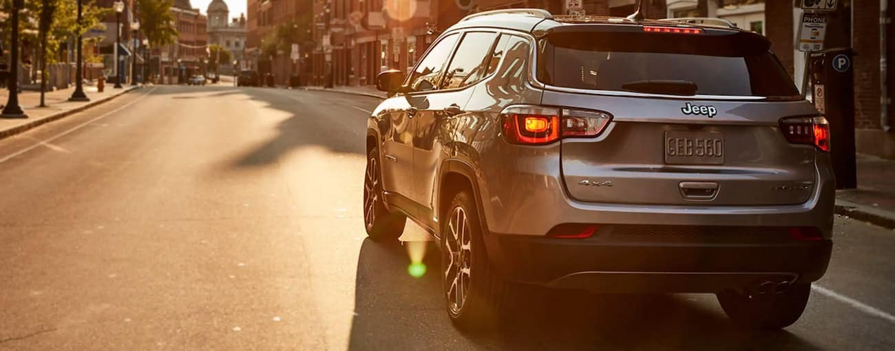 A grey 2021 Jeep Compass is on a city street at sunset.
