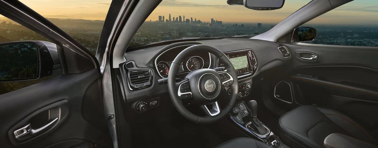 The black interior of a 2021 Jeep Compass is shown with a city in the windshield.