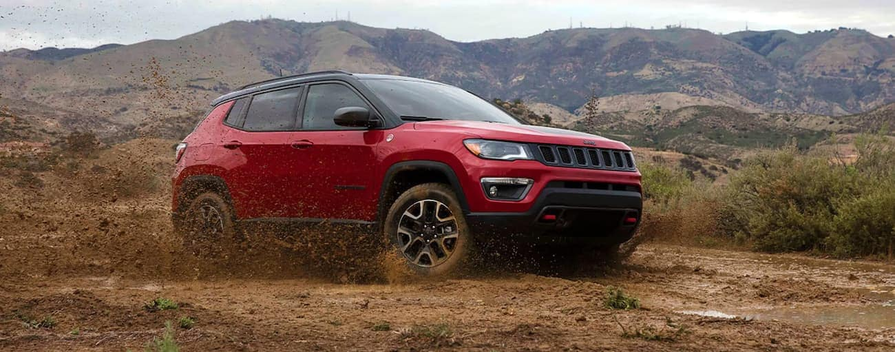 A red 2021 Jeep Compass is off-roading in mud in front of mountains.