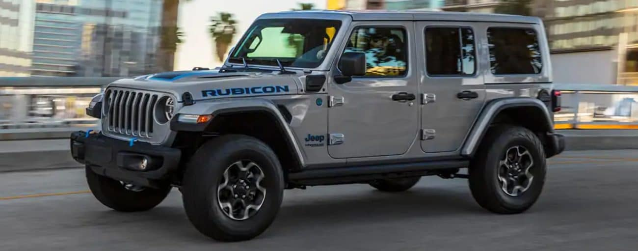 A silver 2021 Jeep Wrangler 4xe is driving on a highway past a city.
