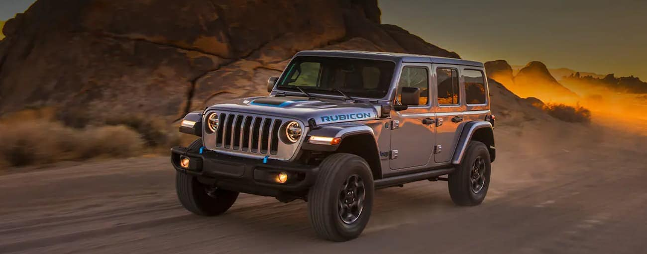 A grey 2021 Jeep Wrangler 4xe is on a dirt road in the desert.