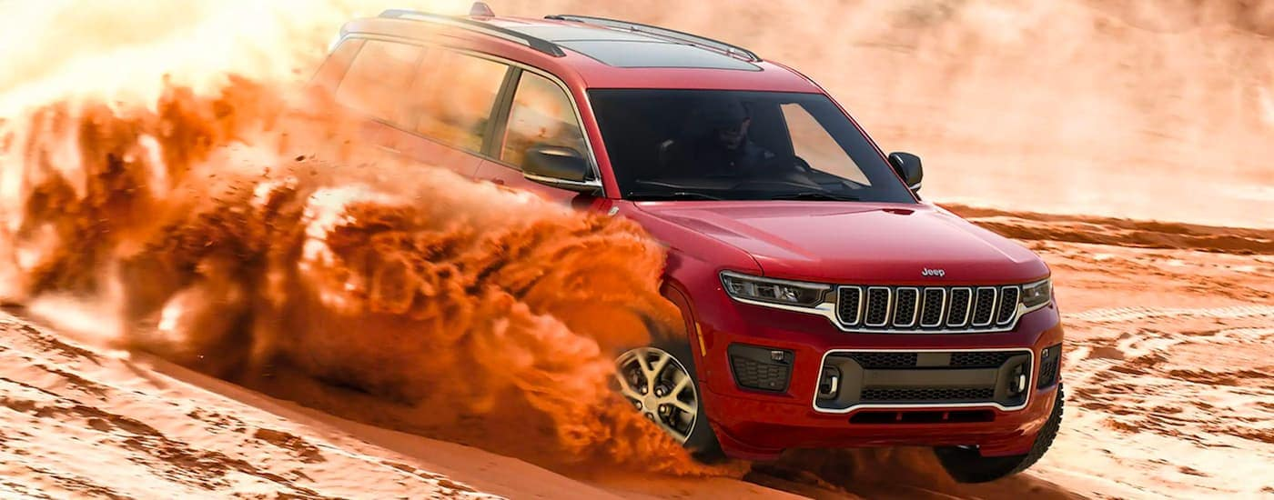 A red 2021 Jeep Grand Cherokee L is shown kicking up sand in the dunes.
