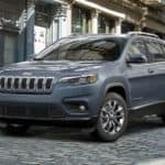 A grey 2021 Jeep Cherokee is shown from an angle parked on a cobblestone road after leaving a Ohio Jeep dealer.
