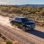 A black 2019 Ram 1500 is shown from a high angle driving down a dirt road after leaving a Ran dealer near Covington.