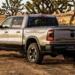 A silver 2021 Ram 1500 is shwon from the rear on a rural dirt road.