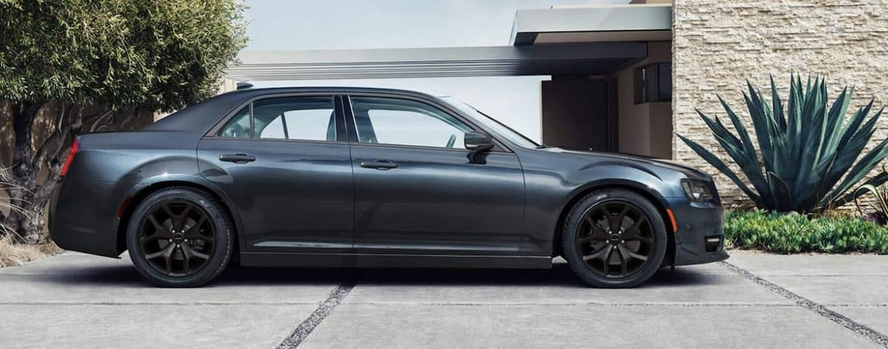 A black 2021 Chrysler 300 is shown from the side parked in front of a modern garage.