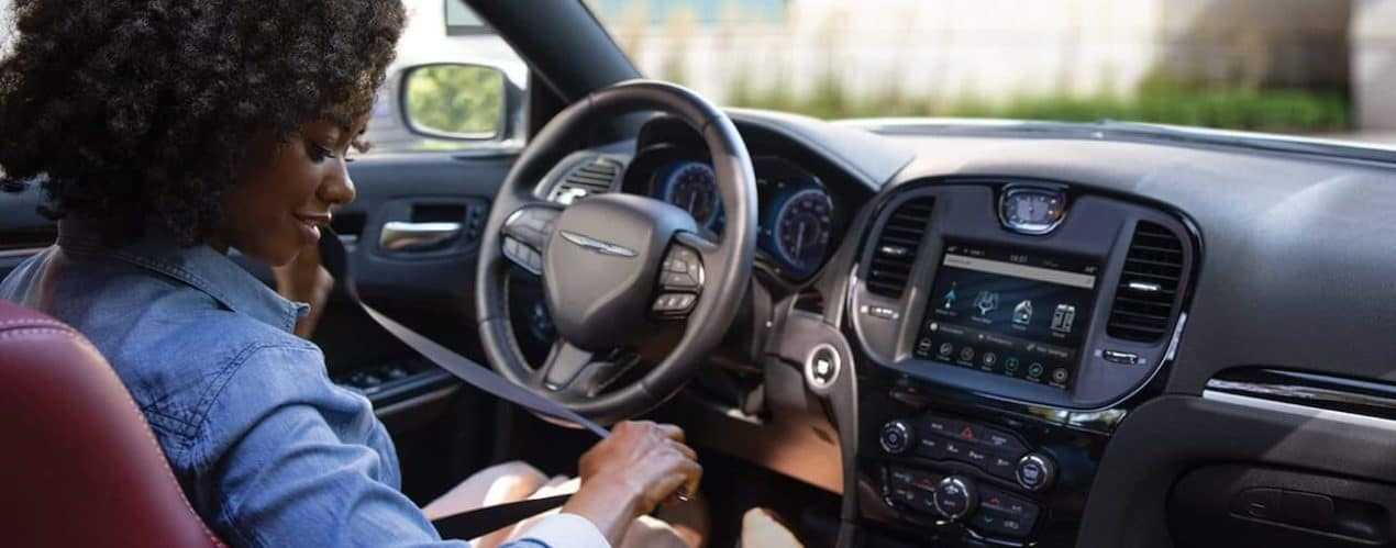 A woman is sitting in the front seat of a 2021 Chrysler 300.
