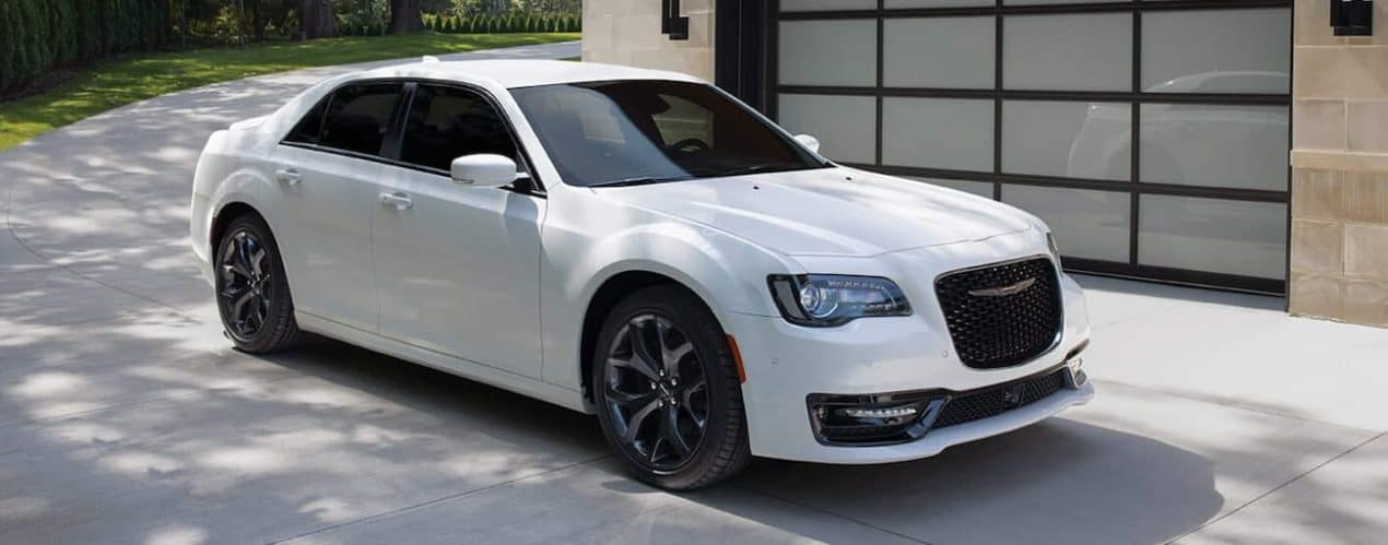 A white 2021 Chrysler 300 is shown parked in front of garage.