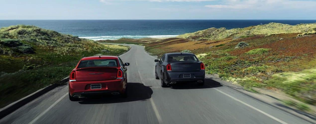 A red and a black 2021 Chrysler 300 are driving on a road to the beach.