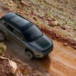 A grey 2019 Jeep Compass is shown from above driving on a dirt road after leaving a pre-owned Jeep dealer.